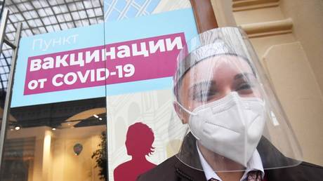 A girl in a protective mask near the coronavirus vaccination center in GUM in Moscow.