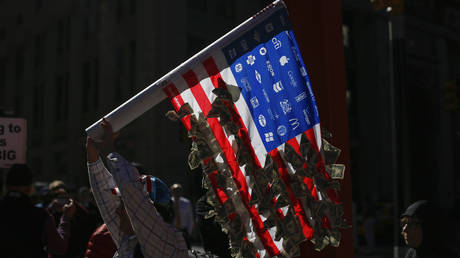 An Occupy Wall Street protester marches outside a barricade at Zuccotti Park in New York, US on September 17, 2013