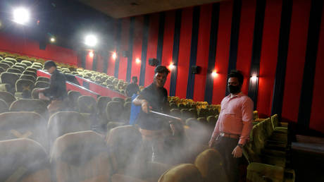 FILE PHOTO: Workers sanitize a hall in City Gold cinema after its reopening, amidst the outbreak of the coronavirus disease (COVID-19), in Ahmedabad, India, October 15, 2020. © REUTERS/Amit Dave