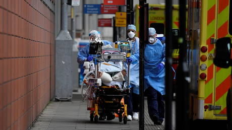 Medical workers move a coronavirus patient in London. (FILE PHOTO)