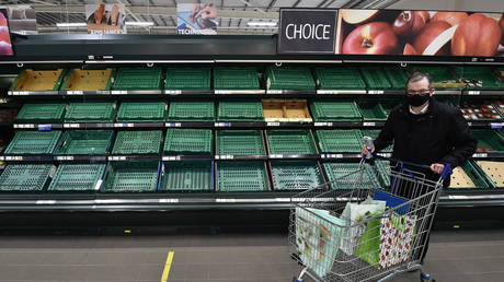 Supermarket shoppers walk past rows of empty shelves in Tescos on January 14, 2021 in Belfast, Northern Ireland