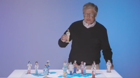 Bill Gates is shown using figurines of humans on a world map to illustrate his proposed global disease alert system.