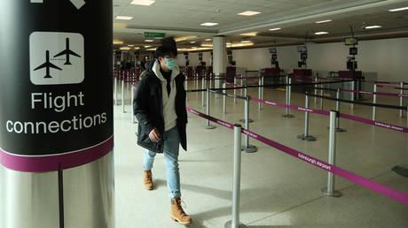 FILE PHOTO: A passenger wears a protective mask as he walks through the Edinburgh Airport amid concerns over the coronavirus disease (COVID-19) spread, in Edinburgh, Scotland Britain March 16, 2020.