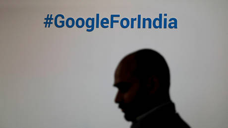 FILE PHOTO. A man walks past a Google hashtag during an event in New Delhi, India.