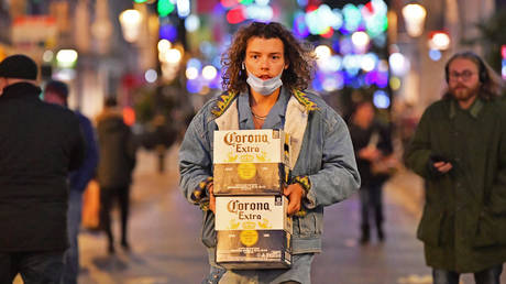 FILE PHOTO: A man carrying beer in Cardiff as pubs, bars, restaurants and cafes are forced to stop selling alcohol and shut by 6pm as part of a new round of coronavirus restrictions that come into force in Wales