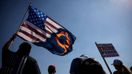 A supporter of President Donald Trump holds an U.S. flag with a reference to QAnon during a Trump 2020 Labor Day cruise rally