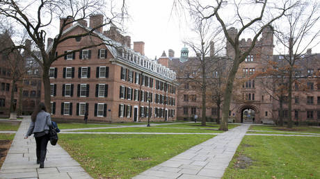 A student is shown walking on the Old Campus at Yale University in New Haven, Connecticut.