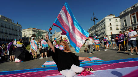 A person wearing a protective face mask waves a transgender pride flag during a demonstration for the rights of transgender people in Madrid, Spain, July 4, 2020 © Reuters / Juan Medina
