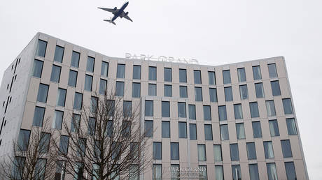 A plane flies over a hotel