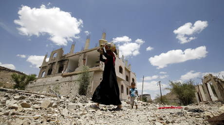 FILE PHOTO: A woman and a boy walk past the ruins of buildings destroyed in Saudi-led air strikes in Yemen's capital Sanaa, September 13, 2015
