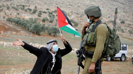 FILE PHOTO: A demonstrator holds a Palestinian flag in front of an Israeli soldier during a protest against Jewish settlements in Beit Dajan in the Israeli-occupied West Bank, 2020 © REUTERS/Raneen Sawafta