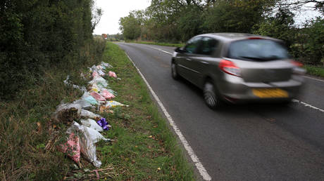 Floral tributes lay on the roadside near RAF Croughton in Northamptonshire at the spot where British motorcyclist Harry Dunn was killed. © AFP / Lindsey Parnaby