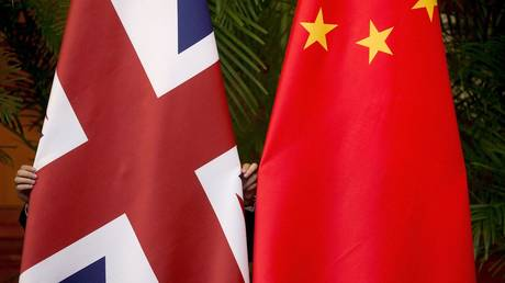 """FILE PHOTO: A worker adjusts British and China (R) national flags on display for a signing ceremony at the seventh UK-China Economic and Financial Dialogue """"Roundtable on Public-Private Partnerships"""" at Diaoyutai State Guesthouse in Beijing, China September 21, 2015"""