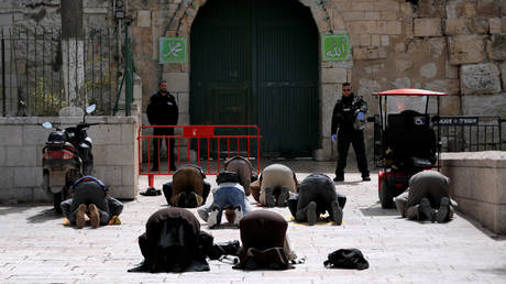 Muslim worshippers pray near a closed gate of the compound housing Al-Aqsa mosque in Jerusalem's Old City after prayers at the compound were be suspended to prevent the spread of the coronavirus. © Reuters / Ammar Awad