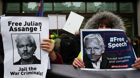 FILE PHOTO: Demonstrators hold placards during a protest outside the Westminster Magistrates Court, where a hearing in the US extradition case against WikiLeaks founder Julian Assange was held, in London, Britain, October 21, 2019.
