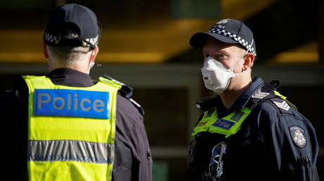 Victoria Police officers meet outside a public housing tower, locked down in response to an outbreak of the coronavirus disease (COVID-19), in Melbourne, Australia, July 8, 2020.