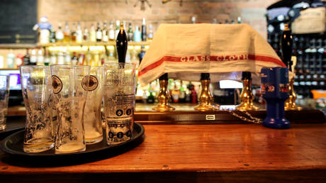 Drinking glasses and a towel over the beer taps are seen after the last orders at The Bridewell pub, amid the outbreak of COVID-19 in Liverpool