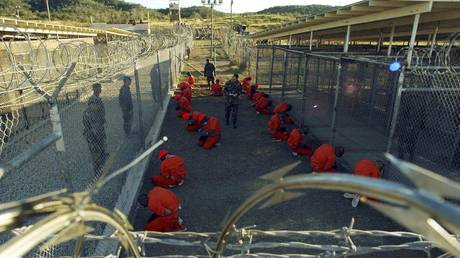 FILE PHOTO: Detainees in orange jumpsuits sit in a holding area under the watchful eyes of military police at Camp X-Ray of Naval Base Guantanamo Bay in Cuba, January 11, 2002.