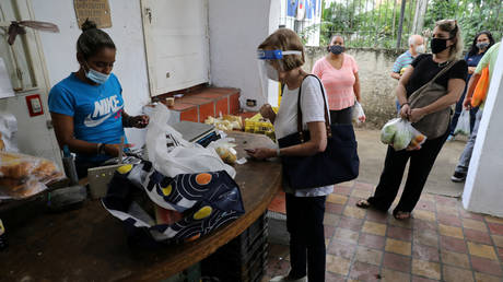 FILE PHOTO: People wearing protective masks due to the coronavirus pandemic queue in an open-air fruit and vegetable market in Caracas, Venezuela.