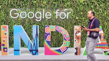 """FILE PHOTO. A man walks past the sign of """"Google for India"""" in New Delhi, India."""