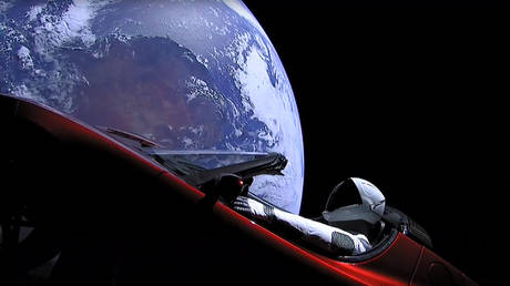 An still from a SpaceX livestream video shows 'Starman' sitting in SpaceX CEO Elon Musk's cherry-red Tesla roadster, after the Falcon Heavy rocket put it into Earth-orbit in February 2018. © AFP / HO / SPACEX