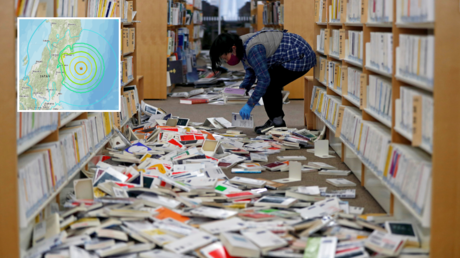 A staff member of library tries to restore books after they fell from book shelves by a strong earthquake at Iwaki City library in Iwaki, Fukushima prefecture, Japan February 14, 2021. © Reuters / Issei Kato