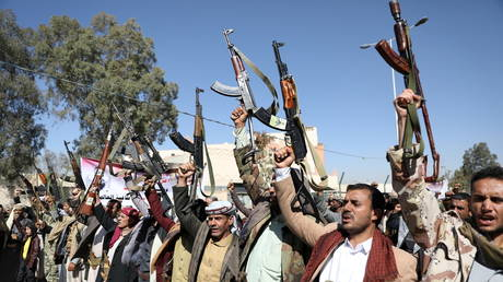 Houthi supporters hold up their weapons during a demonstration outside the US embassy in Sanaa, Yemen January 18, 2021.