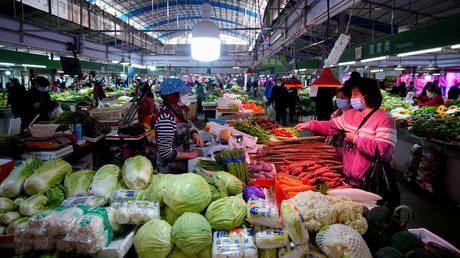 FILE PHOTO: People wearing face masks buy vegetables at a wet market, following an outbreak of the coronavirus disease (COVID-19) in Wuhan, Hubei province, China February 8, 2021