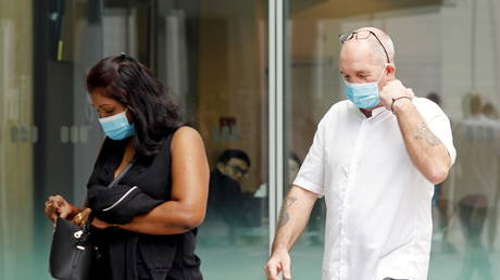 Nigel Skea and Agatha Maghesh Eyamalai arrive for a court hearing after breaking quarantine rules in Singapore, February 15, 2021. © Egdar Su / Reuters