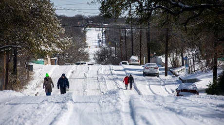 Pedestrians walk on an icy road on February 15, 2021 in East Austin, Texas