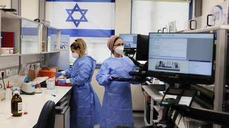 FILE PHOTO: Technicians work at a health facility in Rehovot, Israel.