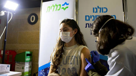 FILE PHOTO: A young woman receives a vaccination against Covid-19. ©REUTERS / Ronen Zvulun