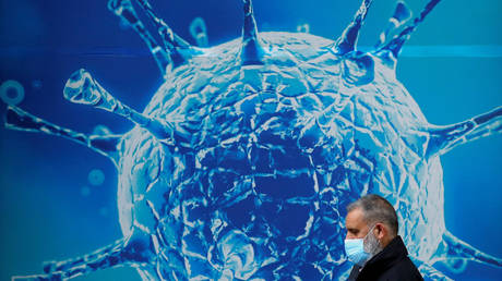 A man wearing a protective face mask walks past an illustration of a virus outside a regional science centre amid the coronavirus disease (Covid-19) outbreak, in Oldham, Britain (FILE PHOTO) © REUTERS/Phil Noble/File Photo