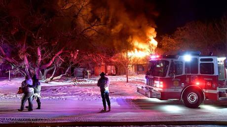 Des résidents de Cedar Crest Drive passent devant leur maison en feu à Abilene, Texas, États-Unis, le 15 février 2021.