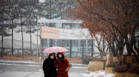 FILE PHOTO. Women wearing face masks walk under an umbrella as it snows in Seoul, South Korea.