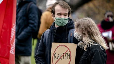 FILE PHOTO: A couple holds a placard during a demonstration against racism at the Koekamp park in The Hague, The Netherlands on December 6 2020.