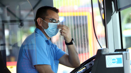 FILE PHOTO: A bus driver wears a mask in Germany, 2020. © Ralph Orlowski / Reuters