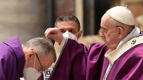 Pope Francis puts ashes on a cardinal's head during the Ash Wednesday mass at St. Peter's Basilica at the Vatican, February 17, 2021.