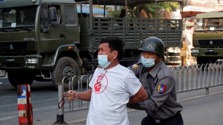 Police detain a man during a protest against the military coup in Mandalay, Myanmar, February 15, 2021