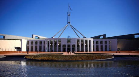 Tourists walk around the forecourt of Australia's Parliament House in Canberra
