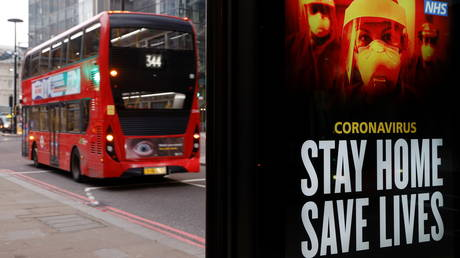 A bus drives past a Government sign about the coronavirus disease in the City of London financial district, Britain, January 8, 2021.