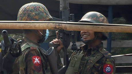 A soldier (R) carries a sniper rifle during a demonstration against the military coup where security forces fired on protesters in Mandalay on February 20, 2021.
