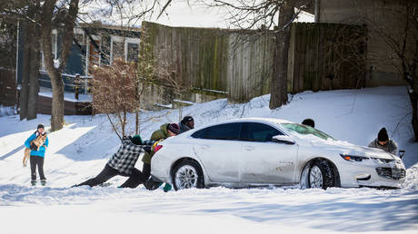Residents push a car out of the snow in Austin, Texas, February 15, 2021. © Montinique Monroe / Getty Images North America / AFP