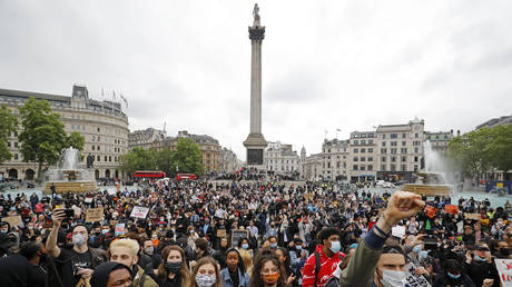FILE PHOTO: Activists, some wearing face coverings or face masks as a precautionary measure against COVID-19, hold placards as they attend a Black Lives Matter protest at Nelson's Column in Trafalgar Square in London on June 12, 2020
