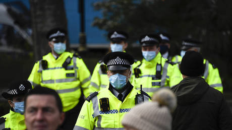 Police officers wear face masks as they patrol an anti-lockdown demonstration in Parliament Square, in London, UK © AP Photo/Alberto Pezzali