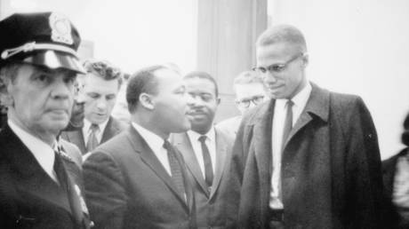 Martin Luther King Jr. and Malcolm X wait for a press conference to begin in an unknown location, March 26, 1964