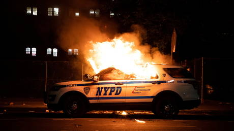 FILE PHOTO: A NYPD police car is set on fire as protesters clash with police during a march against the death in Minneapolis police custody of George Floyd, in the Brooklyn borough of New York City, US, May 30, 2020