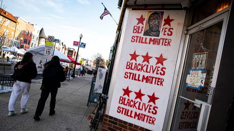People walk past a sign about the Black Lives Matter movement in the Adams Morgan neighborhood, in Washington, US, February 21, 2021