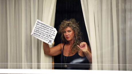 """A woman holds a sign at a window of the Radisson Blu Hotel at Heathrow Airport, as Britain introduces a hotel quarantine programme for arrivals from a """"red list"""" of 30 countries due to the coronavirus disease (COVID-19) pandemic, in London, UK. © REUTERS/Henry Nicholls"""