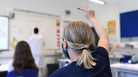 A Year 6 pupil wearing a face mask raises a hand to ask a question in a classroom at the College Francais Bilingue De Londres French-English bilingual school in north London on June 2, 2020 as schools in England partially reopen from coronavirus shutdown. © AFP / DANIEL LEAL-OLIVAS